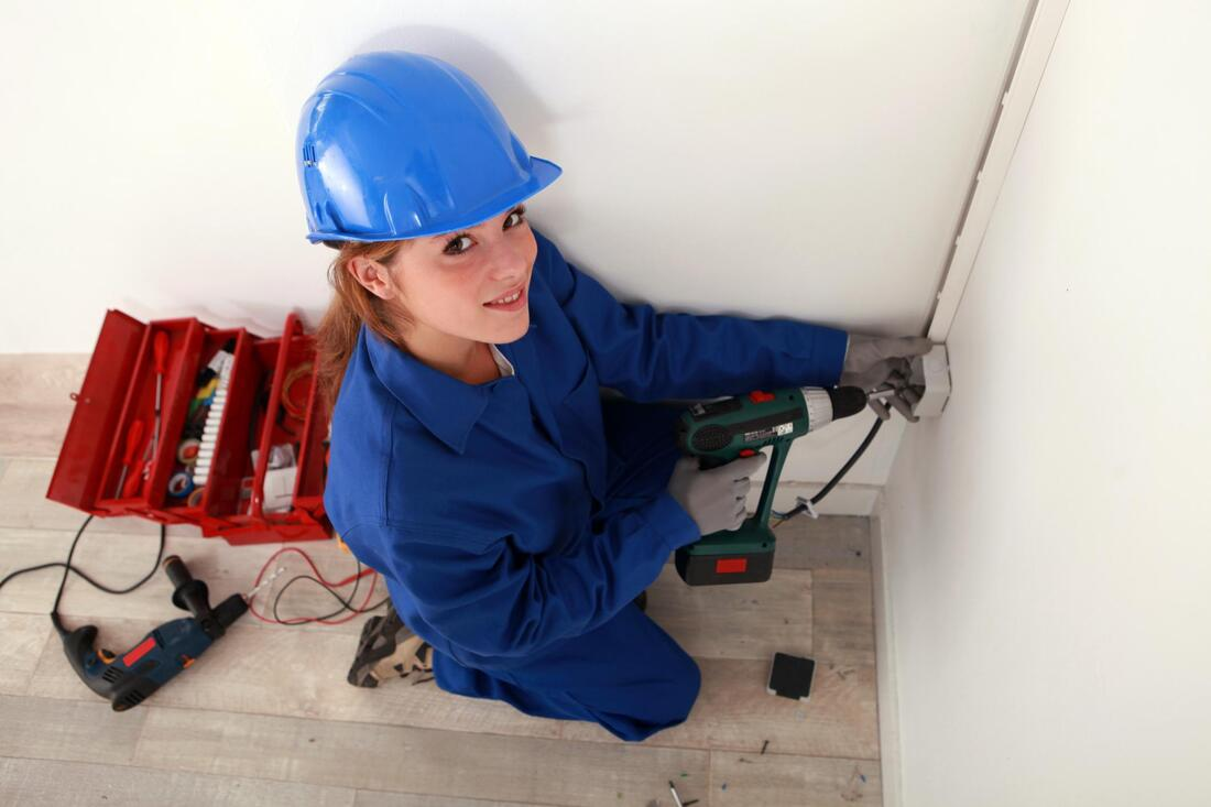 woman drilling a wall
