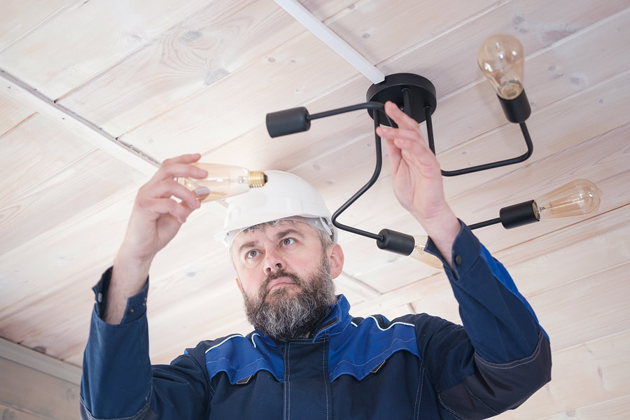 man installing light bulbs